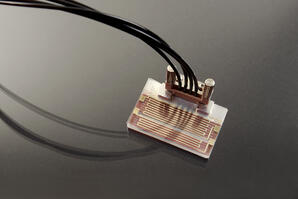 CAPTION: © Fraunhofer IPT ## Photograph of the completed device with gold-printed heaters, microfluidic channels, and fluidics connector.